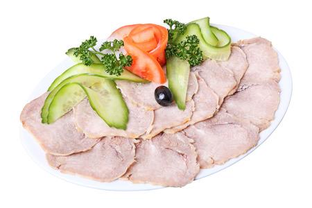 charcutería: rebanadas de lengua con verduras y hortalizas en un plato blanco elíptica aislada en un fondo blanco. Vista lateral. Foto de archivo