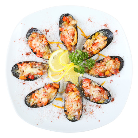 Eight mussel shells with vegetables and cheese on a white dish isolated on a white background. Top view.