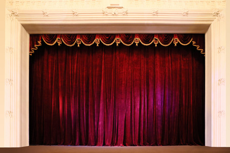 Closed crumpled red curtain over empty theater stage