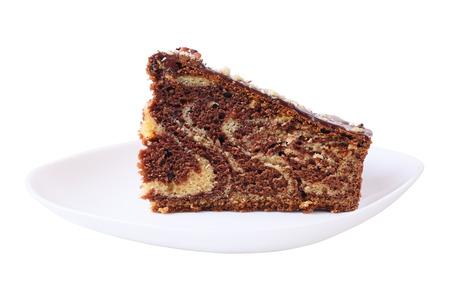 porcion de torta: Un pedazo de pastel de masa de blanco y negro en un plato blanco aislado en fondo blanco. Vista lateral.