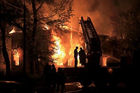 incendio casa: dos siluetas en camión de bomberos en el fondo housefire