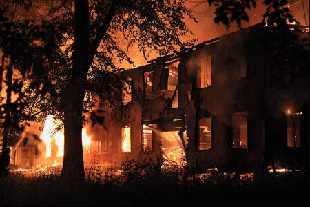 fire damage: burning house in the darkness