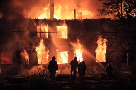 siluety hasičů na hořícího domu na pozadí