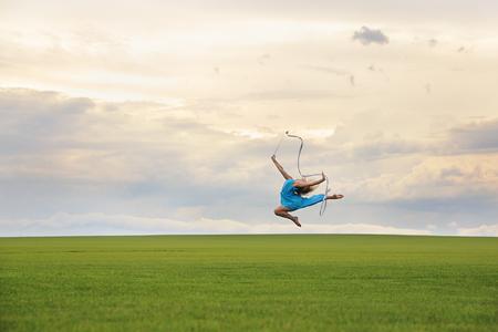 donna che balla: Giovane donna in abito blu con robbon salto in erba su Cloudscape cupo Archivio Fotografico