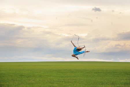 robbon: Young woman in blue dress with robbon jumping on grass over gloomy cloudscape