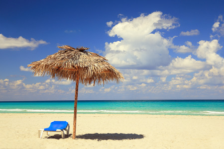 varadero: umbrella of palm leaves and blue deck chair on sand beach