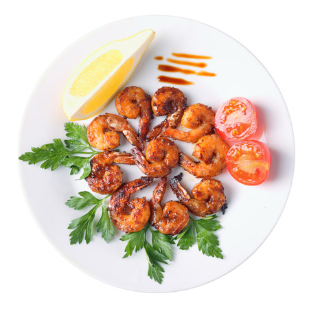 shrimps roasted in teriyaki sauce with  slice of lemon and cherry tomato on a white round dish isolated on white background. Top view.