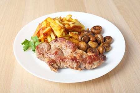 Pork steak with sliced fried potatoes and mushrooms on a white round dish on wooden table. Side view