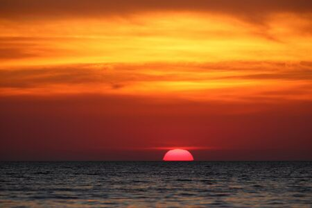 the sun peeks out in the heat above the sea under orange clouds. Cape Tarkhankut, Crimea. Stock Photo