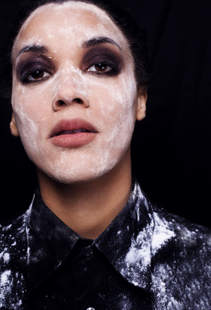 Close up of woman with closed eyes and white beautiful mulatto prints of flour on face on black background photo