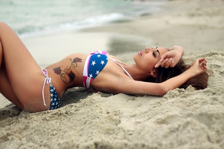 Attractive girl lying on the sand by the sea. Sunny day. photo