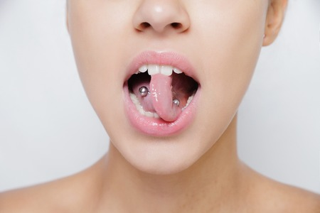 tongue out: Beautiful woman sticking out her tongue and showing her young piercing