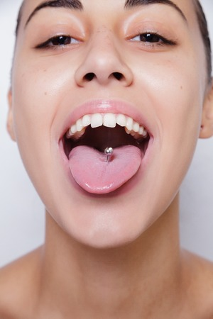 Beautiful woman sticking out her tongue and showing her young piercing