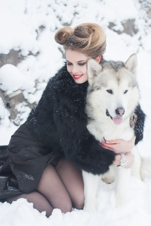 Young woman with wolf dog in snow Stock Photo
