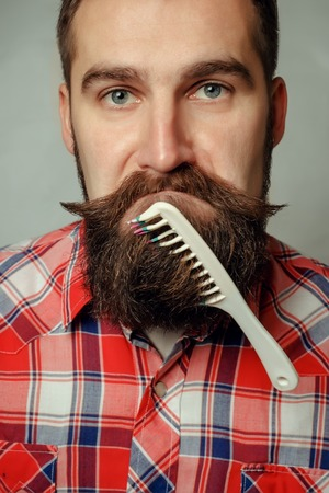 comb: young man comb his beard and moustache on gray background Stock Photo