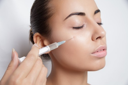 syringe injection: Portrait of young Caucasian woman getting cosmetic injection