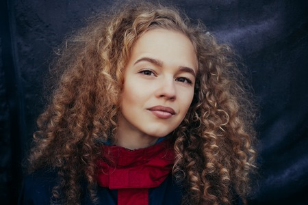Close-up portrait of beautiful model with long curly blond hair on black background