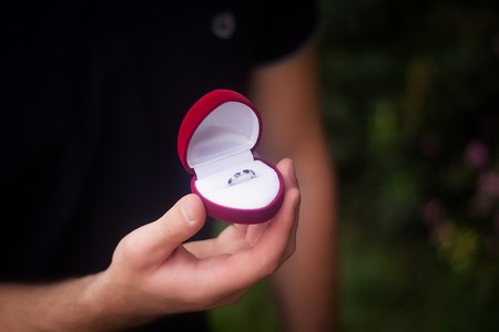 gives: Groom gives the wedding ring in red box Stock Photo