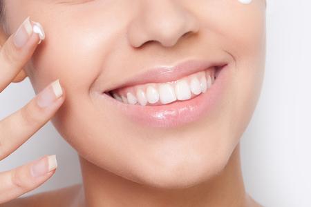piel humana: bella modelo de aplicar el tratamiento crema cosmética en la cara en blanco Foto de archivo