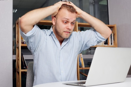 young businessman at his desk looking fearfully  looking at a laptop in his bright office