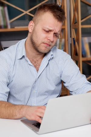 sadly: young businessman at his desk looking sadly looking at a laptop in his bright office