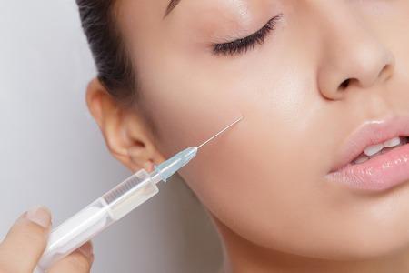 inyeccion: Mujer joven atractiva que consigue la inyección de cosmético, aislado sobre fondo blanco. Médicos manos haciendo una inyección en la cara. Tratamiento de belleza.