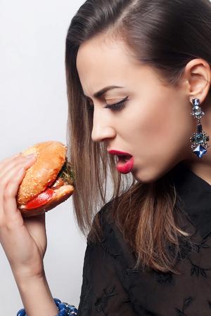 comiendo pan: Primer plano retrato de una hermosa niña morena come una hamburguesa grande. labios rojos, estudio fotográfico