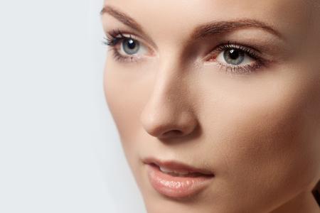 edad media: Hermoso rostro de mujer joven con la piel limpia fresca de cerca aislado en blanco. Retrato de belleza. Hermoso balneario mujer sonriente. Piel Fresca perfecto. Modelo Belleza Pura. Juventud y Cuidado de la piel Concept