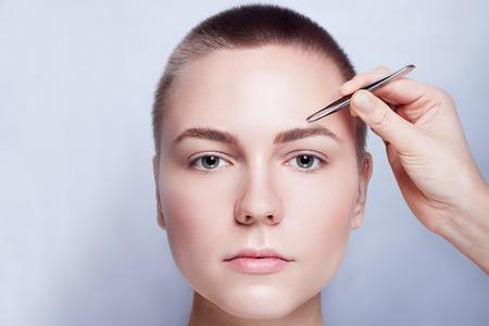 Jonge vrouw met kort haar wenkbrauwen epileren met een pincet close-up, studio snimak. op een lichte achtergrond. Beauty Shot