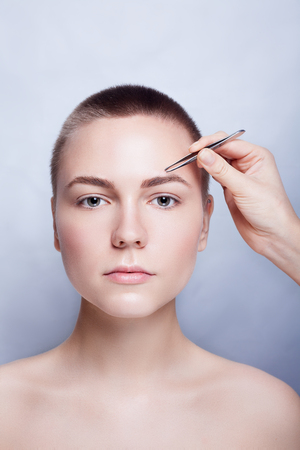 eyebrow: Young woman with short hair plucking eyebrows with tweezers close up, studio snimak. on a light background. beauty shot