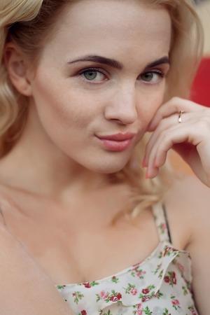 Natuurlijk lichtportret van een gelukkige glimlachende mooie blonde vrouw met blauwe ogen, op achtergrond van fotne de heldere graffiti. hand in de buurt van haar houden