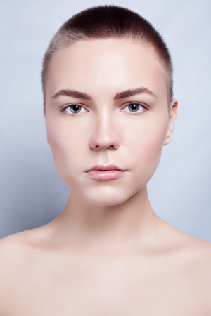 Beautiful Face of Young Woman bald, short hair with Clean Fresh Skin close up. Beauty Portrait. Beautiful Spa Woman Smiling. Perfect Fresh Skin. Pure Beauty Model. Youth and Skin Care Concept