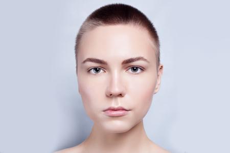 bald: Hermoso rostro de mujer joven calvo, pelo corto con piel limpia fresca de cerca. Retrato de belleza. Mujer hermosa del balneario sonriente. Piel fresca perfecta. Pura belleza del modelo. Juventud y Cuidado de la piel Concept