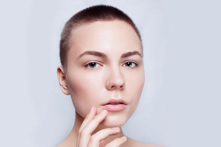 calvo: Hermoso rostro de mujer joven calvo, pelo corto con piel limpia fresca de cerca. Retrato de belleza. Mujer hermosa del balneario sonriente. Piel fresca perfecta. Pura belleza del modelo. Juventud y Cuidado de la piel Concept