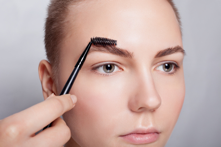 correction: young brunette with short hair woman make-up. girl Cosmetic. Base for Perfect Make-up.Applying Make-up, correction and eyebrow styling. perfect eyebrows