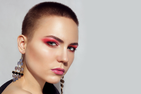 Beautiful fashion model Woman with brunette with short hair and red eyelids. Portrait of glamour girl with bright makeup isolated on white background. Beauty female face close up with perfect make up