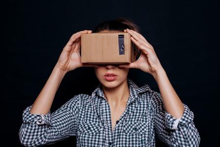 Farbaufnahme eines jungen Frau sucht in einem Karton, ein Gerät, mit dem man virtuelle Realität auf einem beweglichen Telefon zu erleben. Standard-Bild - 52824916