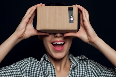 calvo: Color shot of a young woman looking through a cardboard, a device with which one can experience virtual reality on a mobile phone. girl smiling, rejoicing