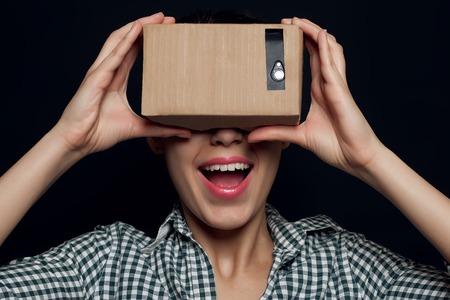 calvo: disparo de color de una mujer joven que busca a través de un cartón, un dispositivo con el que se puede experimentar la realidad virtual en un teléfono móvil. niña sonriente, regocijándose