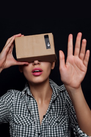 which one: Color shot of a young woman looking through a cardboard, a device with which one can experience virtual reality on a mobile phone. girl touches a hand, finger virtual world