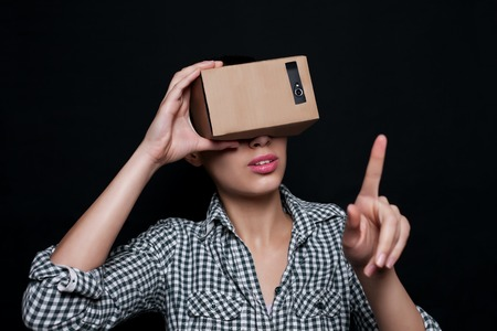 virtual world: Color shot of a young woman looking through a cardboard, a device with which one can experience virtual reality on a mobile phone. girl touches a hand, finger virtual world