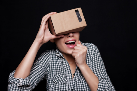 which one: Color shot of a young woman looking through a cardboard, a device with which one can experience virtual reality on a mobile phone. girl is very scared, frightened