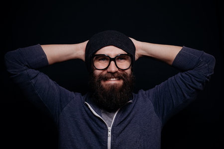 looking directly at camera: Handsome male big beard in glasses and hat, studio shot on black background, looking directly at the camera, man smiling, happy