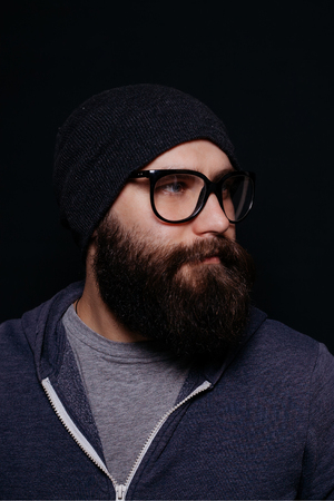 male fashion: Handsome male big beard in glasses and hat, studio shot on black background, man looking away