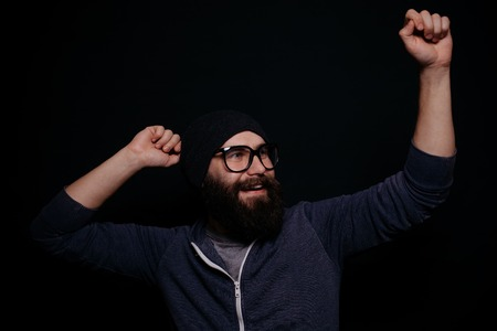 male beauty: Handsome male big beard in glasses and hat, studio shot on black background, man rejoices, dances