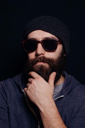 poses de modelos: Apuesto gran barba masculina en vidrios y sombrero, tiro del estudio sobre fondo negro, mirando directamente a la c�mara