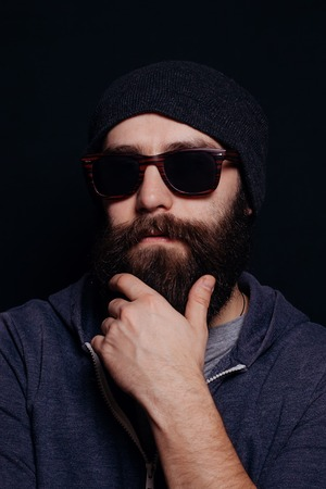 male  man: Handsome male big beard in glasses and hat, studio shot on black background, looking directly at the camera