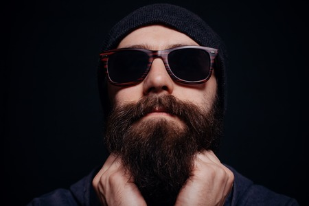 looking directly at camera: Handsome male big beard in glasses and hat, studio shot on black background, looking directly at the camera
