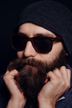 modelos hombres: Apuesto gran barba masculina en vidrios y sombrero, tiro del estudio sobre fondo negro, mirando directamente a la c�mara