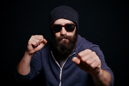 looking directly at camera: Handsome male big beard in glasses and hat, studio shot on black background, looking directly at the camera, aggressive man showing his fists Stock Photo